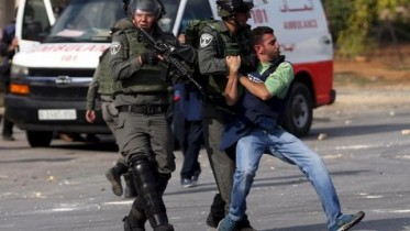 Israeli border policemen beat a Palestinian journalist during clashes with Palestinian protesters near the Jewish settlement of Bet El, near the West Bank city of Ramallah
